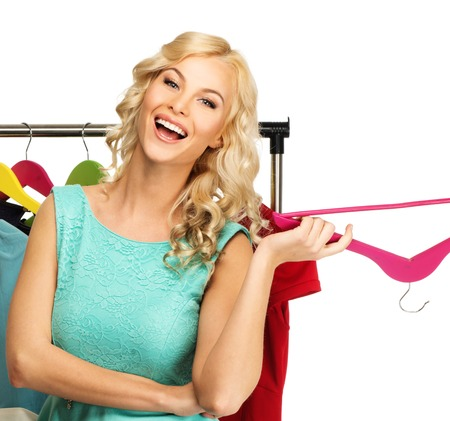 Smiling blond woman choosing clothes on a rack  photo