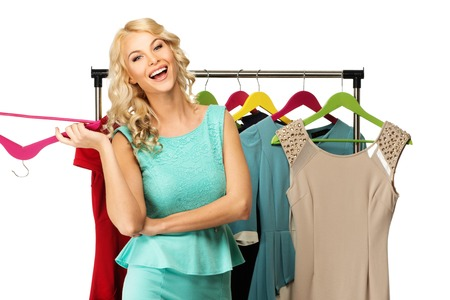 choosing clothes: Smiling blond woman choosing clothes on a rack