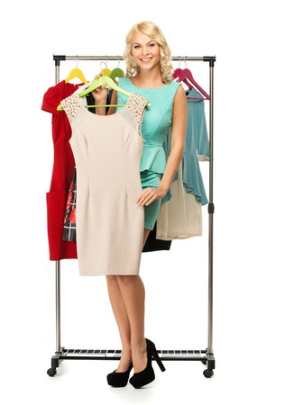 changing clothes: Smiling blond woman choosing clothes on a rack