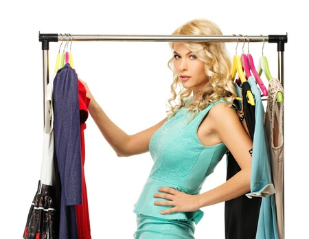 choosing clothes: Blond woman choosing clothes on a rack  Stock Photo