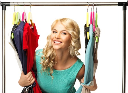 changing clothes: Smiling blond woman among  clothes on a rack