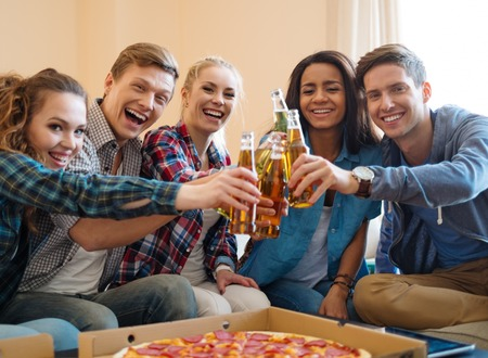 eating pizza: Group of young friends with pizza and bottles of drink celebrating in home interior