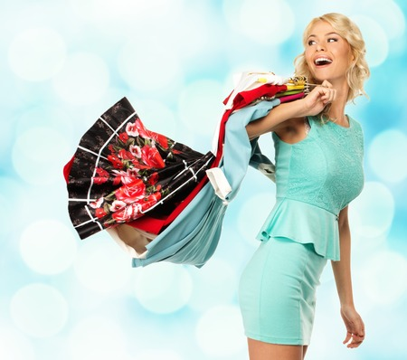 changing clothes: Smiling blond woman with different clothes over blurred background