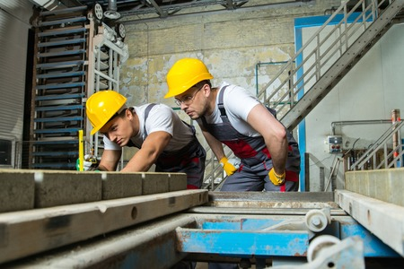 Worker and foreman in a safety hats performing quality check on a factory Stock Photo - 27922506