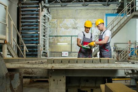 control de calidad: Trabajador y capataz en un sombrero de seguridad que realizan el control de calidad en una f�brica