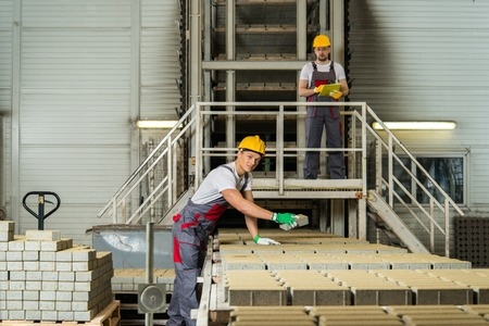 Worker and foreman in a safety hats performing quality check on a factory   Stock Photo - 27922513