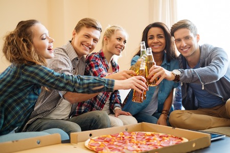 Group of young multi ethnic friends with pizza and bottles of drink celebrating in home interior photo