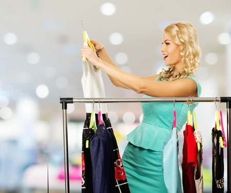 changing clothes: Smiling blond woman choosing clothes on a rack in a shopping mall