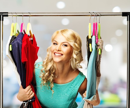 Smiling blond woman choosing clothes on a rack in a shopping mall   photo