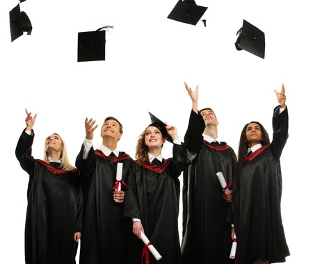 completing: Happy multi ethnic group of graduated young students throwing hats isolated on white Stock Photo