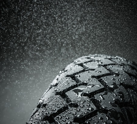 racing track: Close-up shot of classical motorcycle tire tread in wet weather condition  Stock Photo