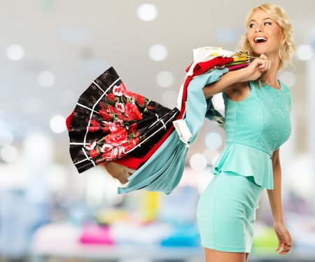 choosing clothes: Smiling blond woman choosing clothes in a shopping mall
