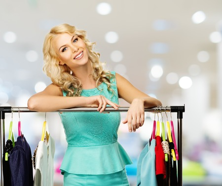choosing clothes: Smiling blond woman choosing clothes on a rack in a shopping mall