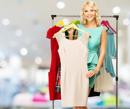woman closet: Smiling blond woman choosing clothes on a rack in a shopping mall