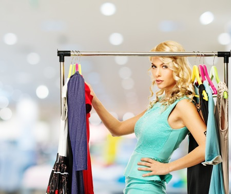 Smiling blond woman choosing clothes on a rack in a shopping mall Stock Photo - 28004157