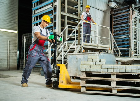 machine operator: Young worker moving paving stones with pallet truck on a factory
