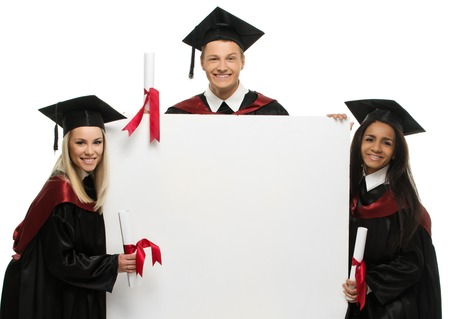 master degree: Multi ethnic group of graduated young students with blank notice board Stock Photo