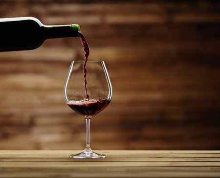 Pouring red wine into the glass against wooden background photo