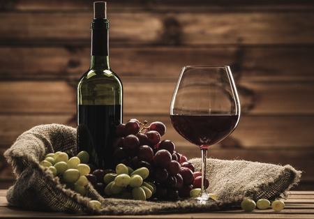 Bottle of red wine, glass and grape on a sack in wooden interior  photo