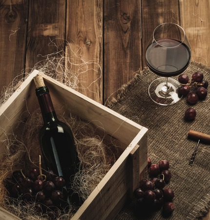 Bottle, glass and red grape on a wooden table  photo