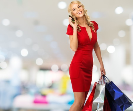 mobile shopping: Happy smiling blond woman with shopping bags and mobile phone in shop interior  Stock Photo