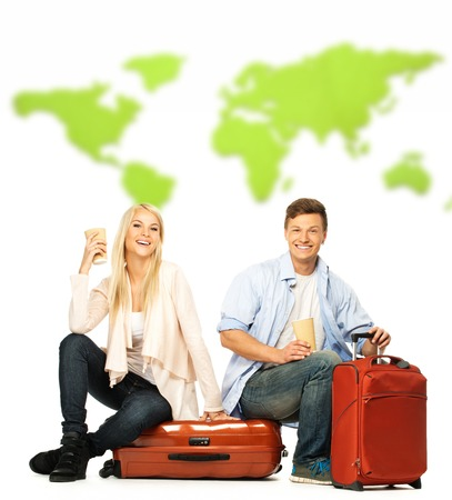 Young couple with coffee cups sitting on suitcases photo