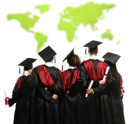 onderwijs: Groep van afgestudeerde jonge studenten in zwarte mantels tegen wereldkaart Stockfoto