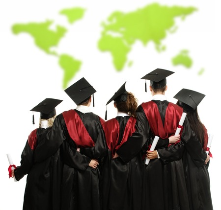 abroad: Group of graduated young students in black mantles against world map  Stock Photo