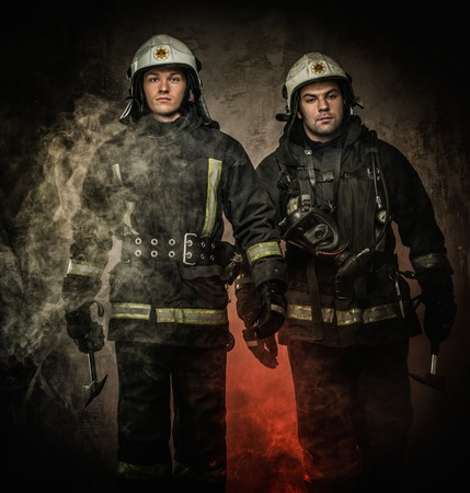 fireproof: Two firefighters with helmet and axe in a smoke