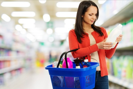 charlady: Beautiful brunette woman with basket reading label on cleanser in a shop