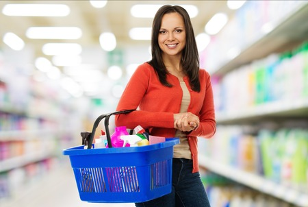 Beautiful cheerful brunette woman with basket full of cleansers in a shop photo