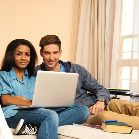 Young multi ethnic students couple preparing for exams in home interior  photo