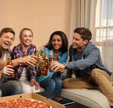 friends party: Group of young friends with pizza and bottles of drink celebrating in home interior