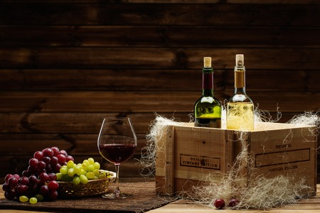Bottles of red and white wine, glass and grape on a wooden interior