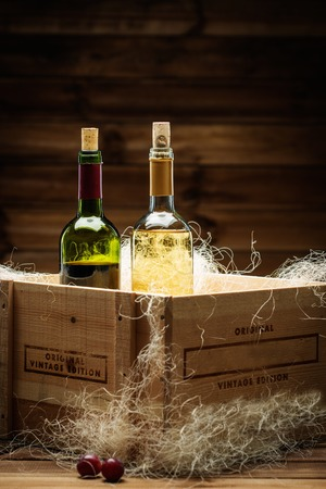 Bottle of red and white wine in wooden box photo