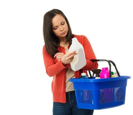 desinfectante: Hermosa mujer morena con la cesta de la lectura de la etiqueta en limpiador