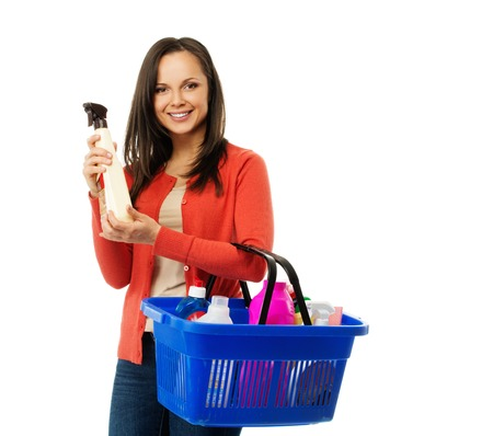 Beautiful cheerful brunette woman with basket full and bottle of cleanser  photo