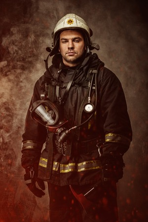 fireproof: Firefighter with helmet and axe in a smoke Stock Photo