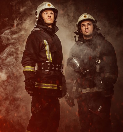 Two firefighters with helmet and axe in a smoke photo