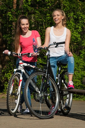 Two happy teenage girls with bicycles in a park  photo