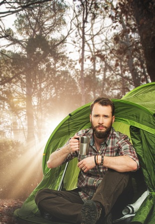 Handsome traveler near tent with coffee cup in autumnal forest photo