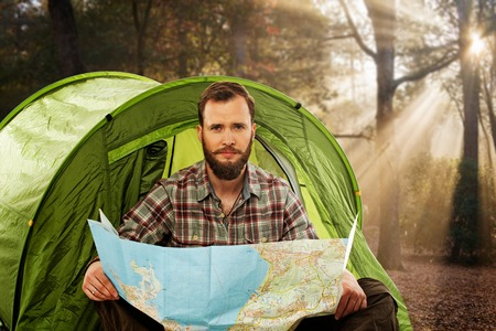 Handsome traveler near tent with a map planning route in autumnal forest photo