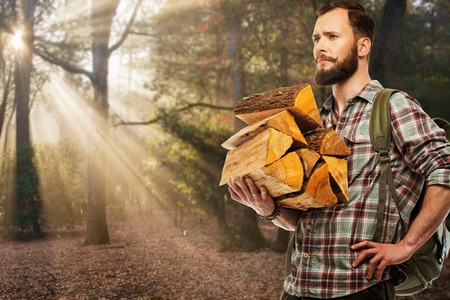 Handsome traveler with backpack and logs for bonfire  in autumnal forest  photo