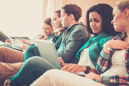studium: Skupina mladých studentů připravuje na zkoušky v bytovém interiéru