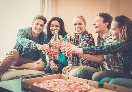 Gruppe der jungen multiethnischen Freunde mit Pizza und Flaschen des Getränks feiert in home interior