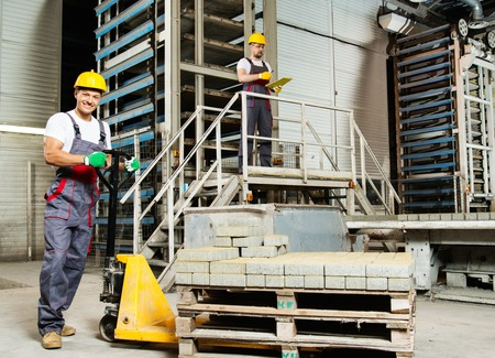 Young worker moving paving stones with pallet truck on a factory photo