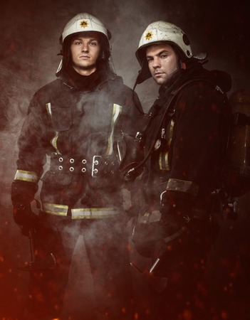 firefighting: Two firefighters with axes in a smoke