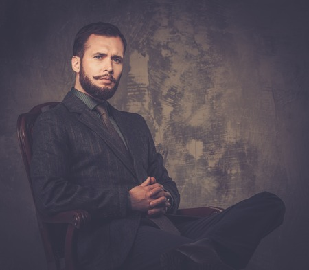 Handsome well-dressed with stick sitting in leather chair  photo