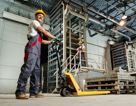 factory production operator young worker moving paving stones with pallet truck on a factory - Production Operator
