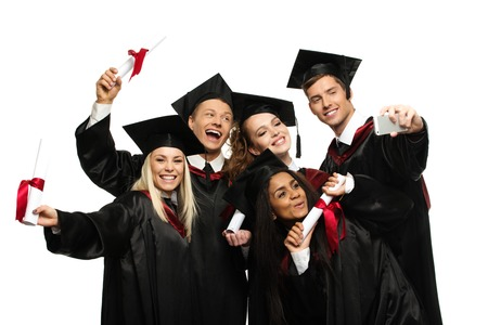 masters degree: Multi ethnic group of graduated young students isolated on white